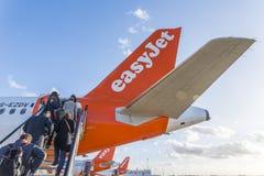 Os passageiros embarcam um avião de Easyjet no aeroporto do ` s Gatwick de Londres Foto de Stock