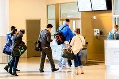 Os passageiros enfileiraram-se na linha para embarcar na porta de partida Imagem de Stock
