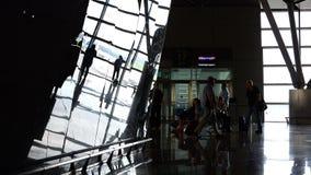 Os passageiros no aeroporto estão sentando-se na área de espera antes de embarcar vídeos de arquivo