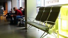 Os passageiros no aeroporto estão sentando-se na sala de espera antes de embarcar o plano filme