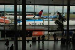 Os passageiros olham aviões estacionados de KLM e de Delta Airlines no aeroporto de Schipol na Holanda Fotografia de Stock Royalty Free