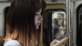 Os passeios no metro que a jovem mulher caucasiano atrativa usa o smartphone escrevem a mensagem vídeos de arquivo