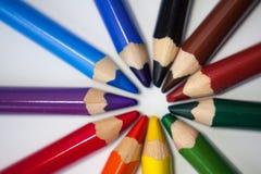Os pastéis coloridos de madeira escrevem no círculo no fundo branco Imagens de Stock Royalty Free