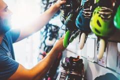 Os patins de rolo da variedade na loja da loja, pessoa que escolhe e para comprar a cor patinam no alargamento do sol do backgrau foto de stock