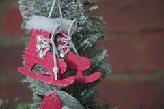 Os patins vermelhos são cinzelados da madeira e decorados à mão DIY para a árvore de Natal Brinquedo para crianças imagens de stock royalty free