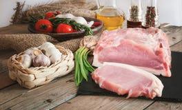 Os pedaços da carne de porco na ardósia embarcam com alecrins foto de stock royalty free