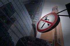 Os pedestres do sinal de estrada são proibidos passar entre os arranha-céus Fotografia de Stock Royalty Free