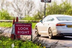 Os pedestres olham Roadworks direitos assinam na estrada BRITÂNICA imagens de stock royalty free
