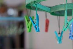 Os Pegs ou os pregadores de roupa de roupa penduram em um cabo Pegs de roupa plásticos Imagem de Stock