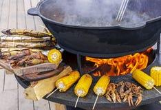 Os peixes, as lagostas e o milho são grelhados em uma grade redonda foto de stock