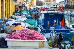 Os peixes coloridos movem o porto na legorne com barco e equipamento de pesca foto de stock