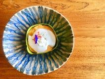 Os peixes cozinhados surram bolos com leite de coco e decoração com a flor fresca dentro da folha da banana posta sobre o prato d fotografia de stock royalty free