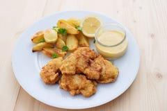 Os peixes de bacalhau nos fritos da massa ou do bacalhau servidos com as batatas cozidas com folhas da salsa e a casa fizeram o m Imagem de Stock