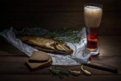 Os peixes fumado Siberian tradicionais envolvidos no papel dos enrugamentos encontram-se na tabela de madeira perto da faca do da Fotografia de Stock