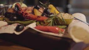 Os peixes grelhados dos salmões serviram com ervas, azeitonas, pimenta de pimentão, e limão que encontra-se no fim do pão árabe a filme