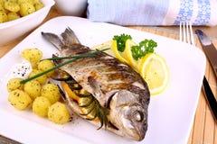Os peixes grelhados seriram com batatas, molho e limão imagem de stock