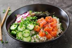 Os peixes salmon havaianos picam a bacia com arroz, rabanete, pepino, tomate, sementes de sésamo e algas Fotografia de Stock Royalty Free