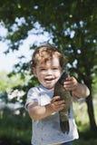 Os peixes travaram nas mãos de um rapaz pequeno de sorriso Um dia de verão ensolarado foto de stock royalty free