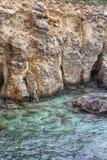 Os penhascos da pedra calcária do litoral de Comino e a lagoa azul clara molham, ilha de Comino, Malta fotografia de stock