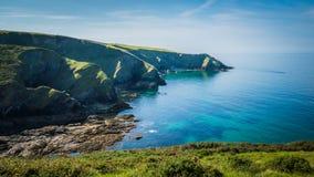 Os penhascos verdes bonitos ajardinam pelo Oceano Atlântico azul perto do cargo Isaac em Cornualha, Reino Unido fotos de stock