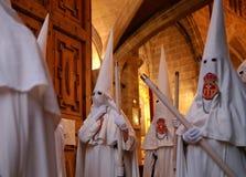 Os penitentes esperam dentro da igreja pelo começo de sua Semana Santa da Páscoa em mallorca fotos de stock