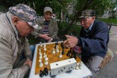 Os pensionista jogam a xadrez no pátio de um prédio de apartamentos Imagem de Stock