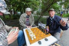 Os pensionista jogam a xadrez no pátio de um prédio de apartamentos Imagem de Stock Royalty Free