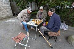 Os pensionista jogam a xadrez no pátio de um prédio de apartamentos Fotografia de Stock Royalty Free