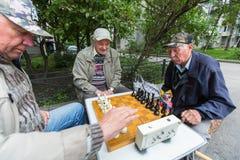Os pensionista jogam a xadrez no pátio de um prédio de apartamentos Fotos de Stock Royalty Free