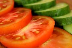 os pepinos e os tomates frescos cortaram em fatias foto de stock royalty free