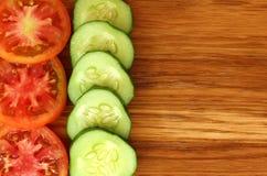 os pepinos e os tomates frescos cortaram em fatias imagens de stock