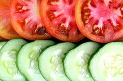 os pepinos e os tomates frescos cortaram em fatias imagem de stock