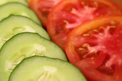 os pepinos e os tomates frescos cortaram em fatias fotografia de stock royalty free