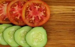 os pepinos e os tomates frescos cortaram em fatias imagem de stock royalty free