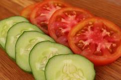 os pepinos e os tomates frescos cortaram em fatias fotos de stock