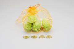 Os pepinos no descanso alaranjado da malha têm moedas de ouro como o primeiro plano Imagens de Stock Royalty Free