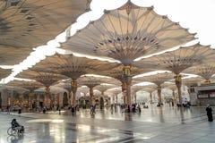 Os peregrinos andam debaixo dos guarda-chuvas gigantes na mesquita de Nabawi Foto de Stock