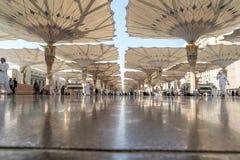 Os peregrinos andam debaixo dos guarda-chuvas gigantes na mesquita de Nabawi Fotografia de Stock