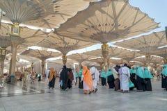 Os peregrinos andam debaixo dos guarda-chuvas gigantes na mesquita de Nabawi Fotografia de Stock Royalty Free