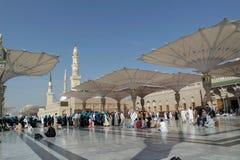 Os peregrinos andam debaixo dos guarda-chuvas gigantes na mesquita de Nabawi Imagens de Stock Royalty Free