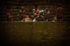 Os peregrinos banham-se e lavam-se nas águas santamente do Ganges, Varana Imagens de Stock Royalty Free
