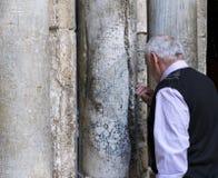 Os peregrinos puseram as mãos sobre colunas na entrada principal da igreja do sepulcro santamente, Jerusalém, Israel, fotografia de stock royalty free