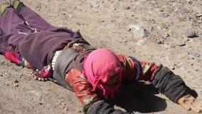 Os peregrinos tibetanos esticam durante o kora em torno do lago Mapam Yumco filme
