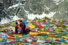 Os peregrinos tibetanos genam e o filho está pendurando as bandeiras Lungta da oração na passagem do La de Drolma Fotos de Stock Royalty Free