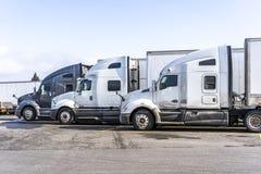 Os perfis de caminhões grandes dos equipamentos semi com semi os reboques estão no parque de estacionamento largo da parada de ca foto de stock royalty free