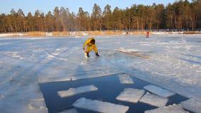 Os pescadores cortaram o gelo no lago para fornecer o oxigênio aos peixes, cortando o gelo em um lago e fazendo respiradouros ao  filme