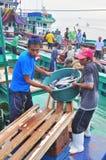 Os pescadores estão aterrando o atum dos barcos de pesca ao mercado Fotografia de Stock