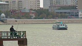 Os pescadores no banco de rio na cidade estacionam Cazaquistão, Atyrau video estoque