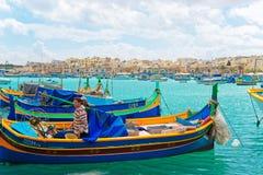 Os pescadores no barco colorido de Luzzu em Marsaxlokk abrigam em Malta Fotografia de Stock Royalty Free
