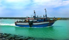 Os pescadores retornam do mar com barco grande imagens de stock